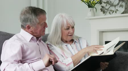 photo album : Mature Couple Sitting On Sofa And Looking At Photo Album Together