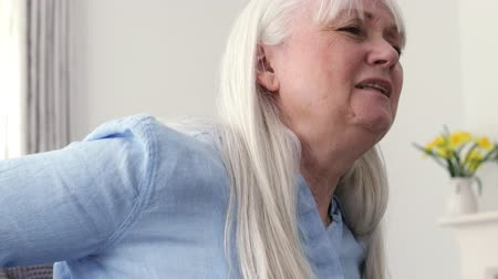 Mature Woman Suffering From Backache At Home Stock Footage