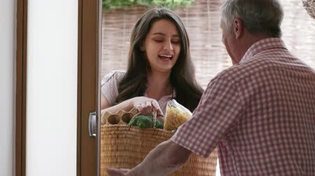 neighbor : Young Female Neighbor Helping Senior Woman With Shopping Stock Footage