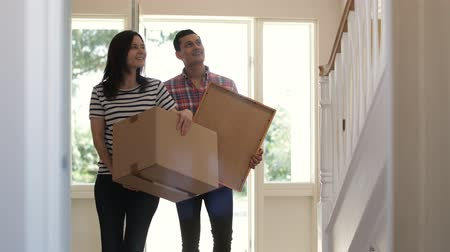 недвижимость : Excited Couple Carrying Boxes Into New Home On Moving Day Shot In Slow Motion