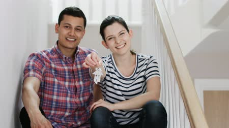 двадцатые годы : Young Couple Sitting On Stairs Holding Keys To New Home Shot In Slow Motion