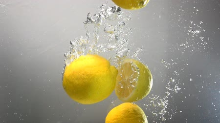 citrón : Whole lemon drops under water. Isolated