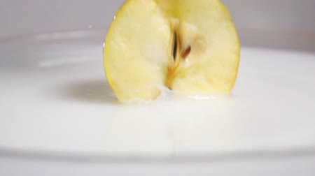 nu : Fresh tasty yellow apple dropping into the white liquid milk in high slow motion. Shot on high-speed camera sony rx 10 ii in 500 fps mode