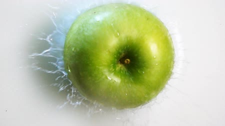 turmix : Tasty healthy green apple falling into the milk with stunning splash. Shot made with high speed camera in slow motion mode. Vertical camira static shooting. Stock mozgókép