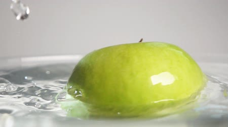 enchimento : Fresh green apple swirling in the transparent water in super slow motion. Sony rx 10 ii isolated on gray background. Vídeos