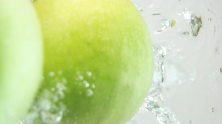 hurl : Two whole fresh tasty green apples plung in water on white background breaking liquid surface with explosive stunning splashes in slow motion. Camera underwater shot. Vertical orientation to the sky.