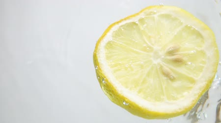 cytryna : Round fresh lemon slice plunging into the transparent water  with explosive stunning splash, breaking the surface of liquid. Underwater high-speed slow motion shot on white background isolated. Camera vertical orientation to the sky.