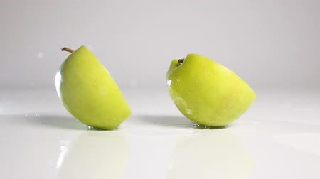 metade : Whole green apple falling down and breaking on two halves on wet white floor bouncing with explosive splash and spray. Shot with high speed camera in slow motion mode. White background isolated.