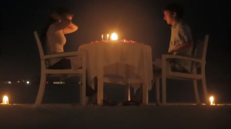 mehtap : Loving couple share a romantic lobsters dinner with candles at outdoor sea beach in water against wonderful night Stok Video