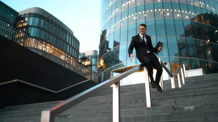 construir : Young successful businessman easy slide on the outdoor stairs rail with smile and jump at the end. Glass business centre building at the background. Teal and Orange style. Wide Ultra HD tripod shot.