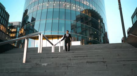 construir : Young successful businessman easy sliding on the outdoor stairs rail with smile and jump at the end. Glossy business centre building at the background. Teal and Orange style. Wide 4k tripod shot.