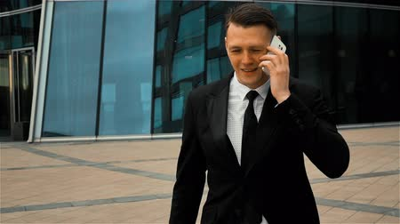 goes : Young successful businessman in black suit and tie goes to work and uses white a smart phone for answering call. Modern glass business centre at the background. Teal and orange style. Super slow motion 250 fps middle steadycam shot.