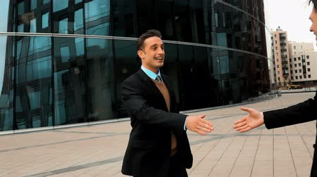podnikatel : Slow motion: two businessman partner in suit shaking hands with smile. Glass business centre building at background. Close-up steadycam shooting.