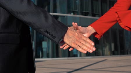 рукопожатие : Slow motion. Cheerful businesspeople, or businesswoman and client handshaking. Manicure. Glass business centre building bg. red and black suit. steadicam close-up shooting