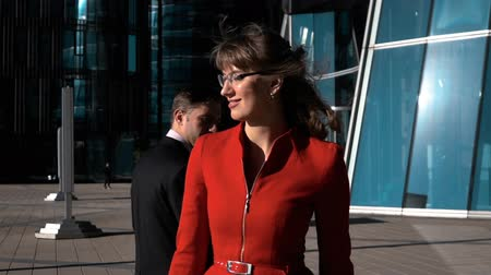 corporate affairs : Slow Motion: Flirting of a business people outdoors, male and female in sexy red suit and glasses look at each other. Tablet pc and smartphone. Glass office building.