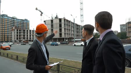 проект : Slow motion. Presentation of the business plan of the new building. Three confident businesspeople. Architector with text tablet in helmet presents to customers their building.