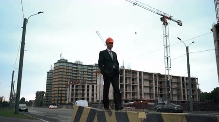 post and beam construction : Young architect in suit and helmet walk on the beam with crane and newly constructed building at the background. Teal and orange style. Static wide shooting Stock Footage