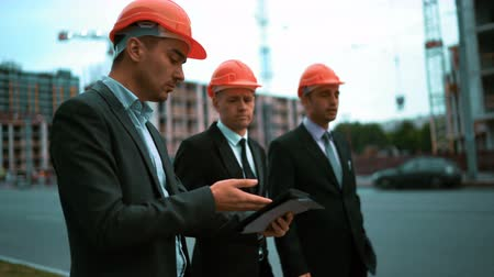 állványzat : Construction worker with digital pad and businessmen in suit and protective helmets talking on site about new construction. Crane and beams at the background. Teal and orange middle stabicam shot.