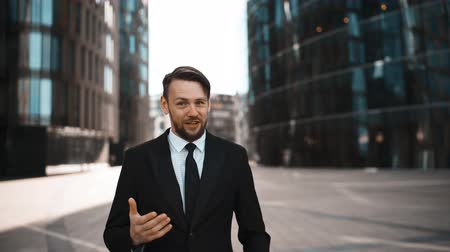 ustawa : Portrait Young successful Businessman approve Your opinion in formal suit and tie with beard and mustache. He gives thumb up and looks happy of praising You friendship and partners in business concept. Modern building bg Wideo