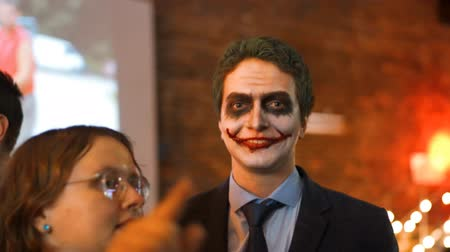 coringa : 4k uhd handy footage. Young attractive guy businessman at the party wear the masquerade costume and grimm of joker with bloody mouse on cheeks. Orange color.