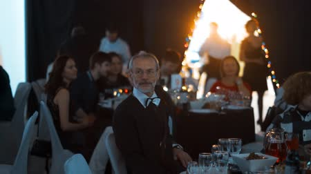 discutir : 4k uhd Old mature man and many young people sitting at the event dark big hall with tables catering banquet waiting for dinner teal orange style. Vídeos