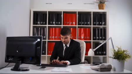 arka görünüm : 4k UHD. Young successful attractive businessman in black suit and necktie work with computer in office white with black and red floders tablet PC documents phone mobile. Smiling at camera.