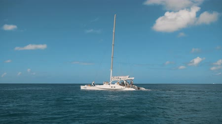 catamaran : Big luxury cataman sailboat catamaran on the horizon in the beautiful Caribbean sea shooting from other boat on the movie midday sunny. Teal and orange 4k ultra hd style. Blue sky with little clouds bg. Stock Footage