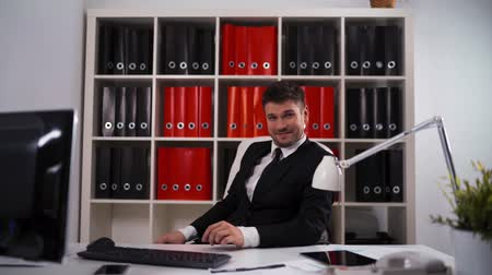 praštěný : 4k ultrahd. Young attractive successful businessman showing you fuck sign with funny smile, third finger inside office with table, computer, digital pad