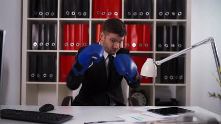 boksör : POV attractive powerful businessman wearing boxing gloves and hitting summon a fight, competition concept inside modern office white red computer, documents.