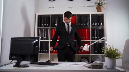 redundancy : ultra hd, businessman with in black suit turning his empty pockets inside out. He stand in office with tablet pc, mobile, phone, computer display, lamp armchair.
