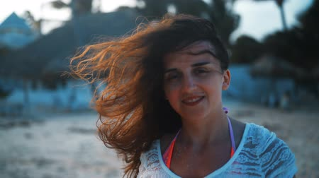 красные волосы : Close up portrait of young seductive brunette woman smiling on camera and laugh, hair blowing in wind. Sunny beach background at sunset. 4k ultra hd handy shot.