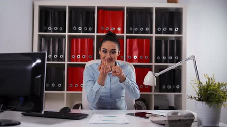 auxiliar : Middle Finger Joke from Businesswoman. Fuck You and smile. Lady in modern office sitting on white armchair. Teal and orange style. End of the work. Friday evening. Stock Footage