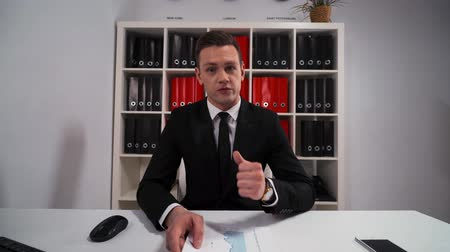 slib : 4k UHD. Attractive, good looking businessman promises to do everything you need in service. POV shooting wide in office. White room with computer mobile phone, tabletPC. Shelf with folders.
