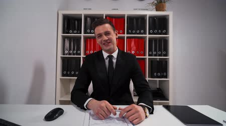 obličejový : 4k UHD. Young successful salesman enrepreneur businessman pointing and laughing with Your funny joke indoor of modern office with table, computer mobile phone and digital pad.