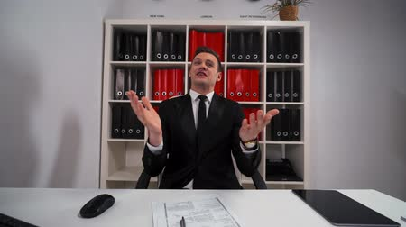 sen : 4k uhd POV. Young stunning attractive Businessman in formal suit black and tie applause You with Your great idea inside clean white modern office with red folders shelf. Wide portrait view. Stok Video