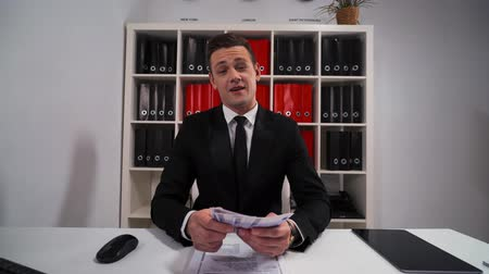 bankier : 4k uhd POV handsome business man in black suit and tie counting euro with smile. The promise that the work and servise will be done. Hide money in pocket. Office indoor. Wideo