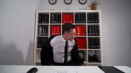 adam : 4k POV. Young attractive Handsome businessman funny dancing in office armchair necktie. He strip remove his black suit. Computer, mouse, keyboard, digital pad, shelf with folders. Wide shot. Stok Video