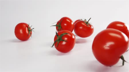 tomate cereja : Many fresh red tasty tomatoes with green tail falling on white surface in super slow motion rapid high speed camera macro.