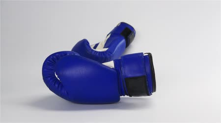 boksör : Slow motion. Vintage dark blue color Boxing gloves falling and bouncing on white surface. Challenge Adversary to fighting concept.