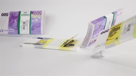 bükülme : Slow motion Few clean Euro money bundles packs falling at white surface with bouncing. 500 and 200 banknotes