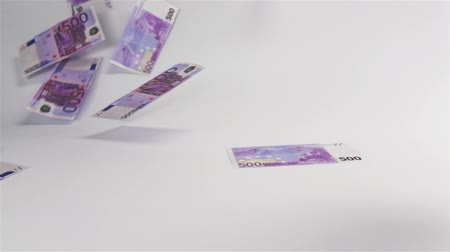 bolsa : Slow motion. Few Euro banknotes flying in the air and landing on white surface