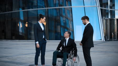 collaborator : Disabled entrepreneur businessman in wheelchair and his collegues has positive conversation with smile and laugh outdoor. They look at camera. 4k uhd Teal and orange shot. Stock Footage