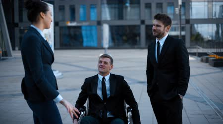haladás : Entrepreneur in wheelchair invalid disabled, but very happy in conversation with his Colleagues businesman and businesswoman in formal suits. Stock mozgókép