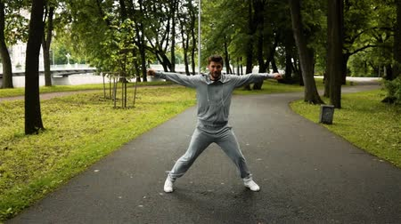 aerobik : young powerful successful man exercising and dancing in green park on asphalt road. Super slow motion high-speed camera phantom flex shot.
