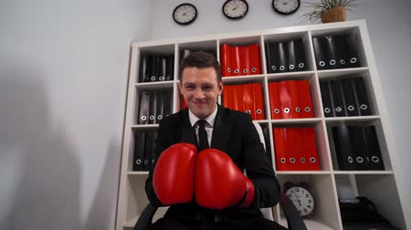 boksör : POV of sitting Angry aggressive businessman entrepreneur with box gloves saying that You will be fail his challenge in boxing or in business. Cut ones throat gesture. 4k ultra hd.