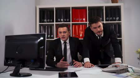bankier : Two businessmen have a big troubles and lost lose big deal while working on computer at desk in office. Losers disappointment concept. 4k UHD Wideo