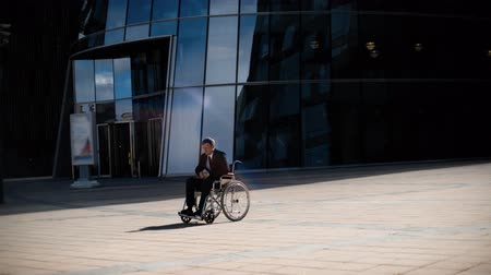 Sad handsome handicapped entrepreneur businessman in wheelchair whith indifferent crowd in business district and modern building teal orange.