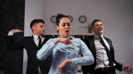 Three joyful businesspeople businesswoman and two businesman dancing cheerfully in office. Wideo