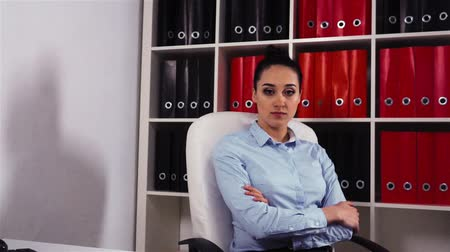 Epic portrait of serious businesswoman in modern office armchair with desktop. Wideo