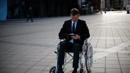 Young smiling disabled businessman sitting in wheelchair outdoor and work with tabletPC outdoor and modern glossy building.